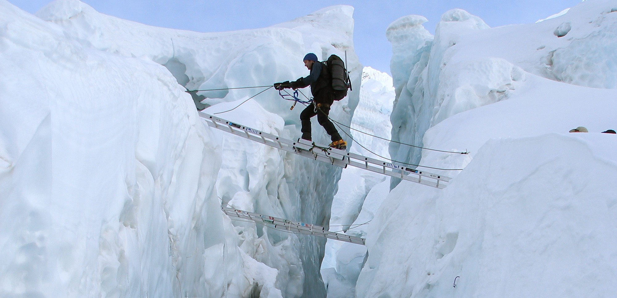 Tom Clowes crossing a crevasse in the Khumbu Icefall on Everest